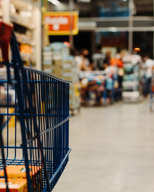 A close-up photo of a grocery shopping cart, with a scene of a grocery store aisle blurry in the background