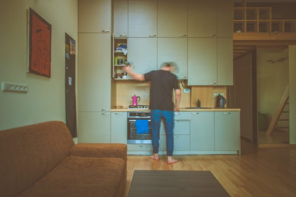 A person is standing in their kitchen. The image is slightly blurred, and so it looks like they are in motion, preparing a meal. The image feels a bit dark, lonely. The kitchen is located near the living room, in what looks like a studio apartment.